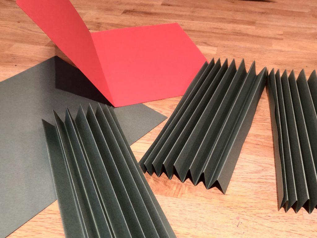 Gevouwen papier en karton om de kerstkaart mee te gaan knutselen.