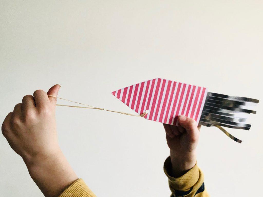 Schiet de vliegend eraket door de kamer met het elastiek